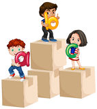 Enfants tenant des alphabets sur des boîtes Photographie stock