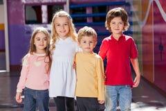 Enfants tenant des bras autour dans le jardin d'enfants Image stock