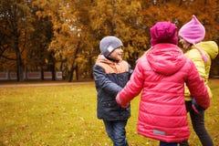 Enfants tenant des mains et jouant en parc d'automne Image libre de droits