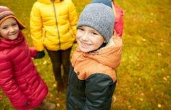 Enfants tenant des mains et jouant en parc d'automne Images libres de droits