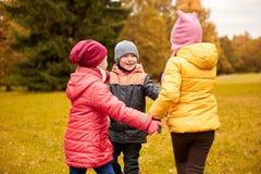 Enfants tenant des mains et jouant en parc d'automne Images stock