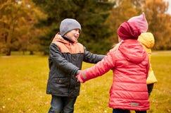 Enfants tenant des mains et jouant en parc d'automne Image stock