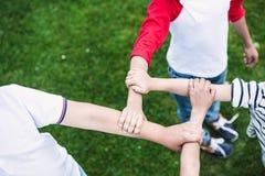 Enfants tenant des mains tout en se tenant sur la pelouse verte en parc Images stock