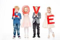 Enfants tenant l'amour de mot Photographie stock