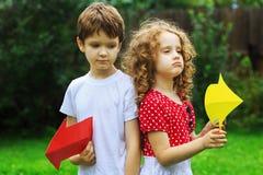 Enfants tenant la flèche de couleur se dirigeant juste et à gauche, en été Photo stock