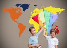 Enfants tenant le cerf-volant devant la carte colorée du monde Photos stock