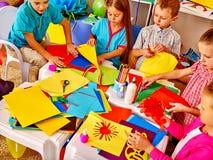 Enfants tenant le papier coloré sur la table dedans Photo stock