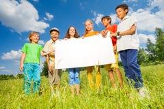 Enfants tenant le papier rectangulaire de forme ensemble Image stock