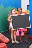 Enfants tenant le tableau noir dans l'école maternelle photo libre de droits