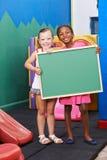 Enfants tenant le tableau noir vide dans le jardin d'enfants Photos libres de droits