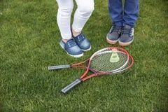 Enfants tenant les raquettes et le volant de badminton proches sur l'herbe verte Photographie stock libre de droits