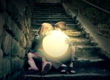 Enfants tenant Sun lumineux sur des escaliers