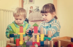 Enfants tranquilles jouant avec les jouets en bois Image libre de droits