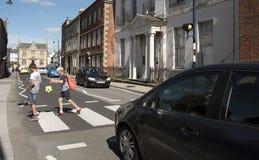Enfants traversant une route à grand trafic Devizes R-U Images libres de droits