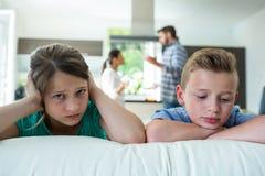 Enfants tristes se penchant sur le sofa tandis que parents discutant à l'arrière-plan Image stock