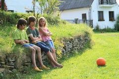 Enfants tristes sur le mur en pierre Photographie stock