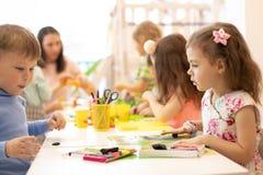 Enfants trois années sur le jeu se développant de classe avec de la pâte à modeler photo stock