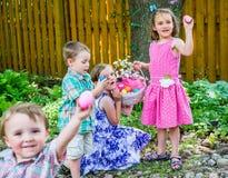 Enfants trouvant des oeufs sur une chasse à oeuf de pâques Photo stock