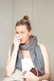 Enfermedad de la mujer en la cama que sopla su nariz Imagen de archivo libre de regalías