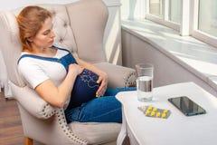 Enfermedad durante embarazo Mujer que se sienta en casa y que toma las drogas m?dicas fotografía de archivo libre de regalías