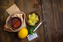 Enfermedad, fríos, curación, caída e invierno del concepto Té con el limón, el termómetro, píldoras y una bufanda hecha punto Vis imagen de archivo