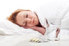 Enfermedad que lucha de la mujer con las píldoras y la reclinación Fotografía de archivo