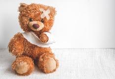 Enfermedades de la niñez del oso de peluche del concepto en el fondo de la materia textil imagenes de archivo