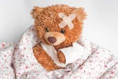 Enfermedades de la niñez del oso de peluche del concepto en el fondo de la materia textil fotografía de archivo libre de regalías