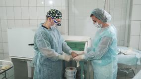 A enfermeira ajuda o cirurgião posto sobre um vestido estéril e luvas Os doutores estão preparando-se para a cirurgia no cirúrgic video estoque
