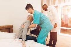 A enfermeira ajuda o homem idoso a sair da cama e a sentar-se em uma cadeira de rodas fotos de stock