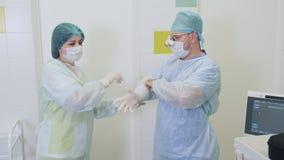 A enfermeira ajuda um cirurgi?o a cal?ar luvas est?reis antes da cirurgia sclerotherapy no hospital video estoque