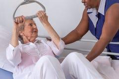 A enfermeira ajuda um paciente a levantar-se no hospital: enfermeira que ajuda a mulher superior a levantar-se com crédito imagem de stock royalty free