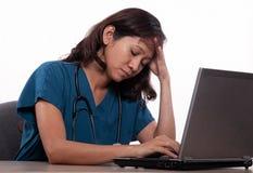 Enfermeira asiática funcionamento cansado no portátil fotografia de stock