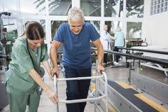 Enfermeira Assisting Senior Man a andar usando o caminhante imagens de stock
