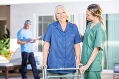 Enfermeira Assisting Senior Woman a andar com Zimmer imagens de stock