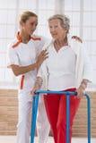 Enfermeira Assisting Senior Woman a andar com Zimmer foto de stock