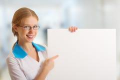 Enfermeira bonita que prende um quadro de avisos em branco Fotos de Stock