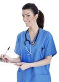 Enfermeira bonito de sorriso que faz lhe anotações médicas Foto de Stock