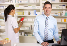 Enfermeira BRITÂNICA e farmacêutico que trabalham na farmácia Fotografia de Stock