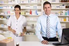 Enfermeira BRITÂNICA e farmacêutico que trabalham na farmácia imagens de stock