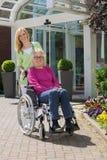 Enfermeira com a mulher superior na cadeira de rodas fora fotografia de stock