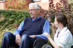 Enfermeira Comforting Senior Man na cadeira de rodas foto de stock