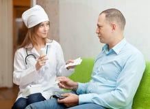 A enfermeira dá ao paciente a medicamentação Fotos de Stock Royalty Free