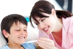 Enfermeira de sorriso e seu paciente com um termômetro Imagens de Stock
