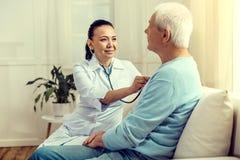 Enfermeira de sorriso que escuta a batida do coração do paciente aposentado fotos de stock royalty free