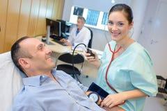 Enfermeira do retrato que realiza a verificação de pressão sanguínea Fotografia de Stock Royalty Free