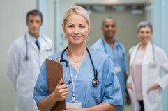 Enfermeira e trabalhos de equipa dos jovens foto de stock
