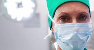 Enfermeira fêmea na máscara cirúrgica no teatro de operação filme