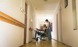 Enfermeira f?mea que empurra o paciente masculino superior deficiente que senta-se na cadeira de rodas fotografia de stock