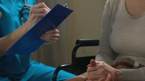 Enfermeira fêmea que enche-se nos papéis, pondo a mulher com a inabilidade sobre a lista voluntária vídeos de arquivo